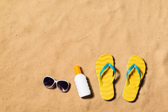 summer-vacation-composition-with-pair-of-yellow-flip-flop-sandals-sunglasses-and-sun-cream-on-a-beach-sand-background