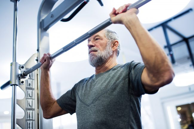 graphicstock-fit-senior-man-in-sports-clothing-in-gym-working-out-doing-pull-ups-on-horizontal-bar